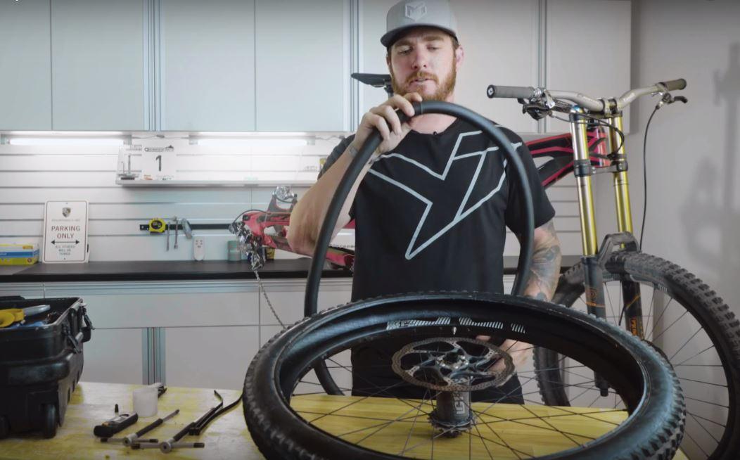 """John Hall, Mechaniker von Aaron Gwin hält die Schaumstoff Einlage, genannt """"Flat Tire Defender"""" in der Hand."""